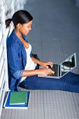 pretty female african american student using laptop