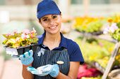 happy young nursery worker holding flowers in greenhouse