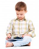 Young boy is using tablet while sitting on floor, isolated over white