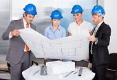 Architects Wearing Blue Hardhat Looking At Blueprint