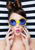 Attractive surprised young woman wearing sunglasses on striped background, beauty and fashion concep