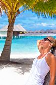 Cute blond girl leaned on palm tree and looking on the sun through sunglasses, summer time vacation,