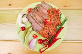 hot roast corned beef on green plate with red spiced tomato sauce over wooden table
