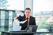Young business man in office throwing papers around