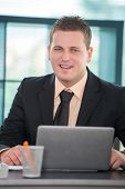 Smiling businessman with laptop posing