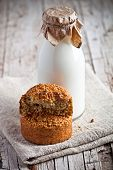 bottle of fresh milk and fresh baked bread on wooden background