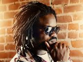 stock photo of swag  - serious black man with dreadlocks - JPG