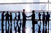 Two businessmen shaking hand in the office building admist other business people.