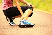 picture of ankle shoes  - young woman runner hold her twisted ankle