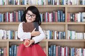 stock photo of indian apple  - Adorable little girl standing in library while holding a book and apple - JPG