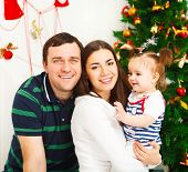 stock photo of christmas baby  - Happy young family with Christmas baby near the Christmas tree - JPG