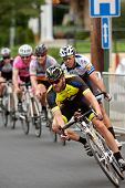 Pack Of Cyclists Lean Into Turn In Criterium Event