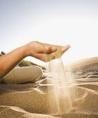 Pacific Islander man spilling sand out of hand
