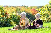 Young Children Having Fruit Picnic At Apple Orchard
