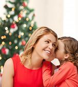 christmas, x-mas, happiness concept - mother and daughter whispering secret