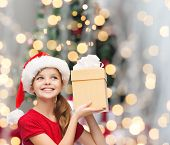 christmas, holidays, childhood and people concept - smiling girl in santa helper hat with gift box over christmas tree lights background