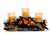 image of centerpiece  - Three flaming candles on a centerpiece of pine and gold foliage - JPG