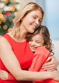 christmas, x-mas, happiness concept - hugging mother and daughter