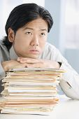 Asian businessman leaning on stack of paperwork