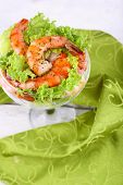 Fresh boiled prawns with lettuce in a goblet on a wooden table on dark grey background