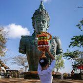 BALI, INDONESIA - SEPTEMBER 19, 2014: A devotee carries a fruit basket as offerings to Lord Vishnu at the Garuda Wisnu Kencana at Uluwatu, Bali Island.