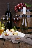 Supper consisting of Camembert and Brie cheese, honey, wine and grapes on sackcloth on stand and win