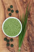 Chlorella tablets, spirulina powder and wheat grass over olive wood background.