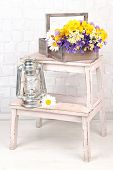 Beautiful flowers in crate with kerosene lamp on ladder on light background