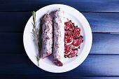 French salami on plate on dark blue wooden background