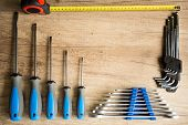 Set of different construction tools on a wooden background.