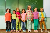 Kids stand in line near the blackboard and smile