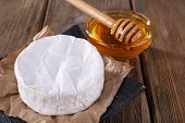 Camembert cheese on paper on plate and honey in glass bowl on wooden background