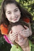 Hispanic girl covering mother's eyes
