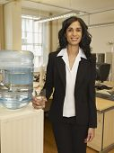 Hispanic businesswoman standing next to water cooler