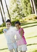 Hispanic sisters spraying hose