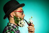 Extravagant man with a beard of flowers wearing elegant bowler hat and smoking a pipe.