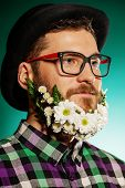 Funny young man with a beard of flowers wearing elegant bowler hat and glasses.