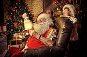 Santa Claus in his everyday clothes in Christmas home d�?�©cor. Happy little boy helps Santa Clau