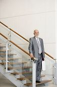 Senior African businessman standing on stairs