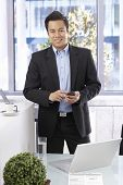Happy smiling businessman holding mobilephone, looking at camera, standing at desk.