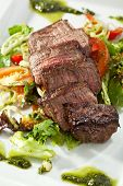 Sliced Beef Steak on Fresh Salad Leaf with Pesto Sauce