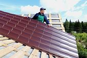 Worker Puts The Metal Tiles On The Roof Of A Wooden House