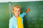 Boy with chalk stands near blackboard and looking