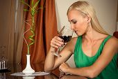 beautiful woman smelling a wine in a glass