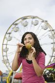 Mixed Race teenaged girl eating candied apple