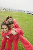 Middle Eastern woman giving sister piggy back ride