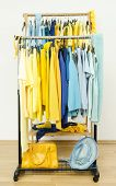 Wardrobe with shades of yellow and blue clothes on hangers.