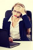 Business woman at call center is having headache. She's sitting by the table with laptop. Isolated on white.