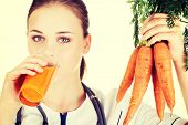 Female doctor holding healthy carrots and juice. Isolated on white.