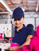 pretty female factory worker sewing garment